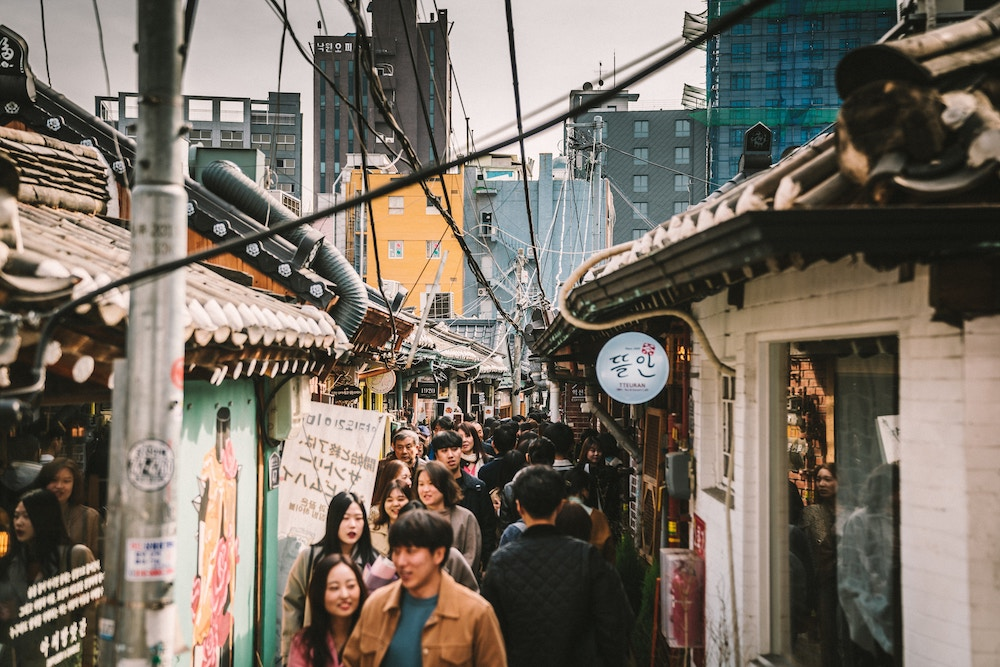 A group of people walking down a crowded Seoul street